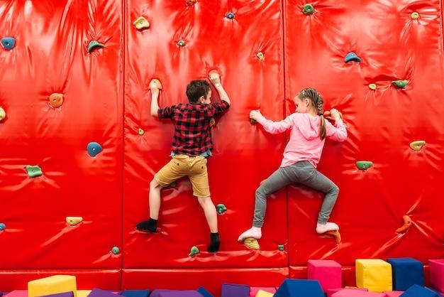 Aktive kinder, die auf einer wand im kinderattraktionsspielplatz klettern. unterhaltungszentrum. glückliche kindheit
