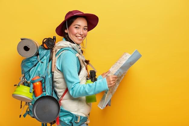 Aktive koreanische touristin trägt einen großen rucksack, trägt einen hut und freizeitkleidung, hält eine karte, studiert die route und hat auf reisen viel zu tun
