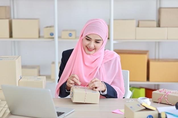 Aktive lächelnde asiatische muslimische frau im blauen anzug sitzend und arbeitend