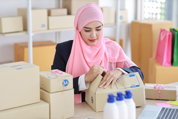Aktive lächelnde asiatische muslimische frau im blauen anzug sitzt und arbeitet mit online-paketbox-lieferung. freiberufliches kmu-startup-mädchen, das auf computer und handy mit glücklichem gesicht arbeitet.