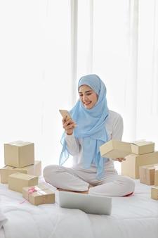 Aktive lächelnde asiatische muslimische frau in der nachtwäsche, die auf bett mit handy und computer sitzt. freie freiberufliche kmu-frau des startups, die mit online-paketzustellung, e-commerce-konzept arbeitet.