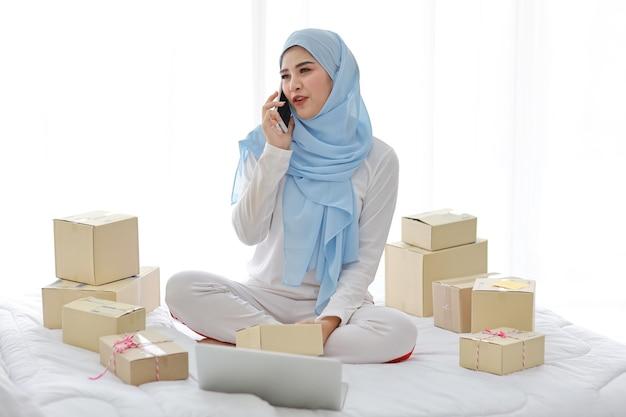 Aktive lächelnde asiatische muslimische frau in der nachtwäsche, die auf bett mit handy und computer sitzt