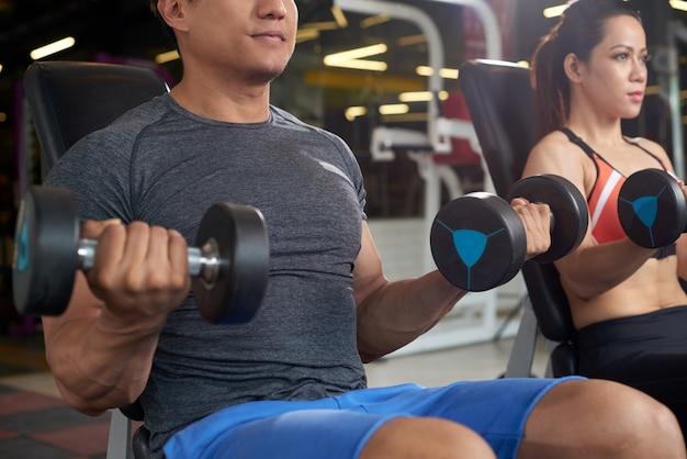 Aktive leute, die anhebendes gewicht der turnhallenübung tun