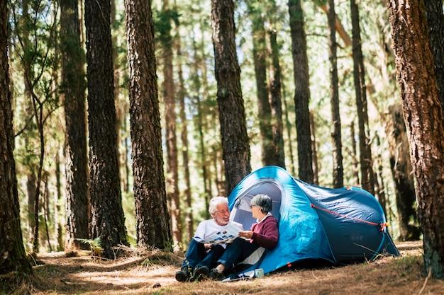 Aktive menschen im alten kaukasischen seniorenpaar reisen mit campingzelt - setzen sie sich in den wald und haben sie gemeinsam spaß - beziehungskonzept für reisende fernweh im ruhestand mann und frau