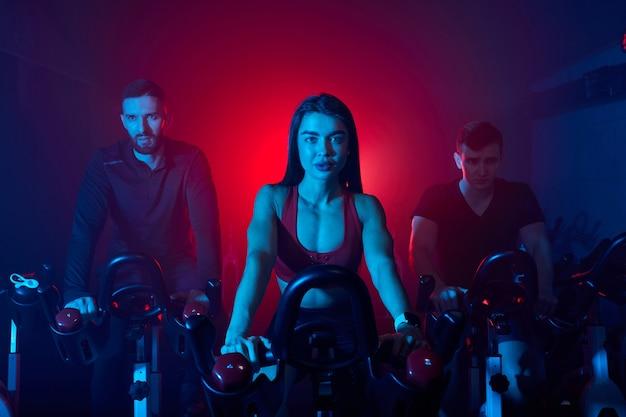 Aktive menschen trainieren an sportgeräten im fitnessstudio, freuen sich zuversichtlich und tragen trainingsanzüge im blau neonbeleuchteten raum 8ik,