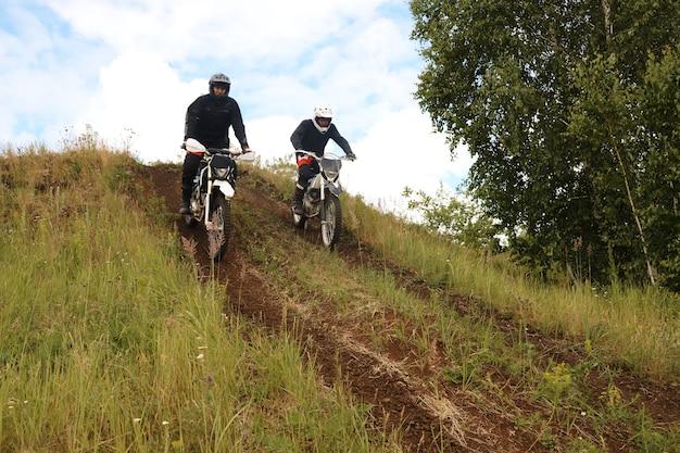 Aktive motorradfahrer in helmen, die mit dem motorrad bergab fahren und gleichzeitig ihre fähigkeiten im gelände entwickeln