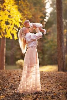 Aktive mutter, die mit kleinem kind im park spielt mutter, die baby in der herbstlichen waldlandschaftsnatur hält