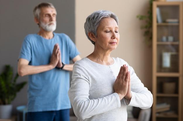 Aktive senioren, die zu hause yoga machen