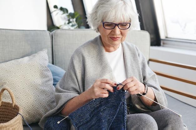 Aktive talentierte kaukasische frau am ruhestandstag drinnen verbringen, warme kleidung für enkel stricken, auf sofa in gemütlichem interieur sitzen, lächelnd. handarbeit, handwerk und hobbykonzept