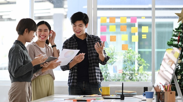 Aktive teamarbeit junger asiatischer designer, die zusammen mit der diskussion über die projektgeschäftsaufgabe arbeiten und brainstorming betreiben.