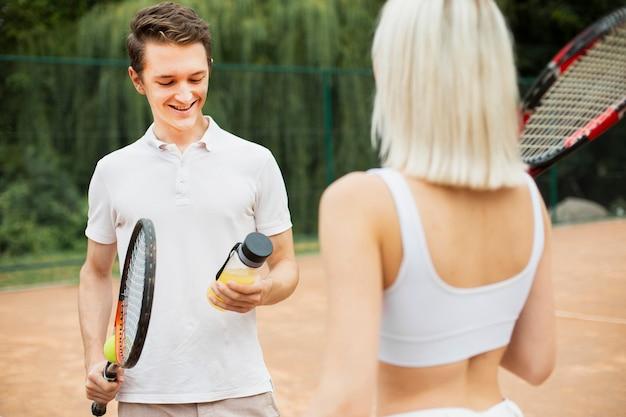 Aktive tennispaare, die eine pause machen
