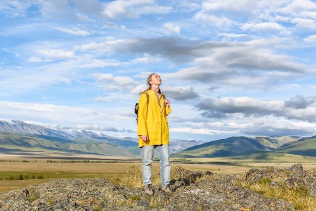 Aktive touristin mit rucksack genießt die schönheit der berge