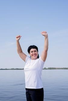 Aktive und glückliche ältere frau, die nahe am flussufer stehend mit den armen oben trainiert