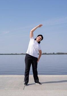 Aktive und glückliche ältere frau, die nahe dem flussufer trainiert