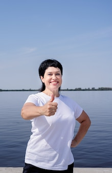 Aktive und glückliche ältere frau in sportbekleidung, die daumen hoch zeigt, die nahe dem flussufer trainieren