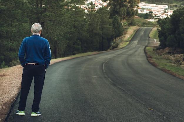 Aktiver älterer mann, der auf einsamer straße zwischen bergen steht