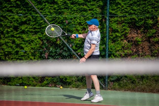 Aktiver älterer mann, der das tennis im freien, rentner-sportkonzept spielt