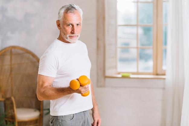 Aktiver älterer mann, der mit dummköpfen trainiert
