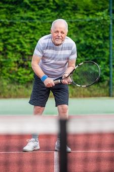 Aktiver älterer mann, der tennis auf dem platz, sportkonzept, gesunden lebensstil spielt