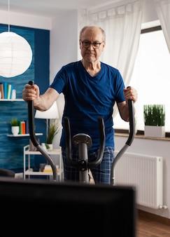 Aktiver älterer mann trainiert beine muskelwiderstand radfahren fahrradmaschine im wohnzimmer während des lebens...