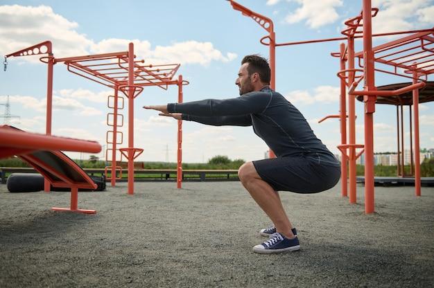 Aktiver athlet in sportlicher uniform, der während des trainings auf einem outdoor-sportplatz kniebeugen durchführt. junger mann beim sport auf dem sommersportplatz. gesundes und aktives lifestyle-konzept