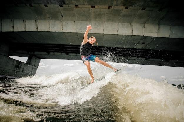 Aktiver athletischer kerl, der auf dem brett hinunter den fluss gegen die betonbrücke wakesurfing ist