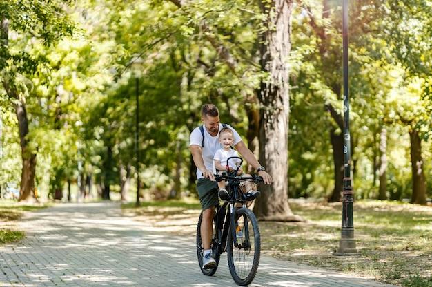 Aktiver familienurlaub und passende freizeitkleidung. ein männliches kleinkind und ein vater fahren mit dem fahrrad durch den park. radurlaub und aktivwochenende. kleinkind sitzt im korb auf dem fahrrad und lacht mit papa