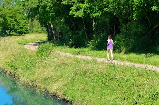Aktiver frauenläufer, der nahe kanalfluss, im freien laufend, sport, fitness und gesundes lebensstilkonzept joggt