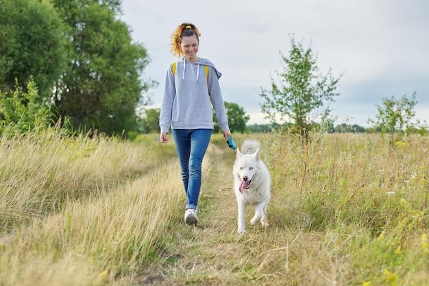 Aktiver gesunder lebensstil, jugendlich mädchen, das mit weißem huskyhund geht
