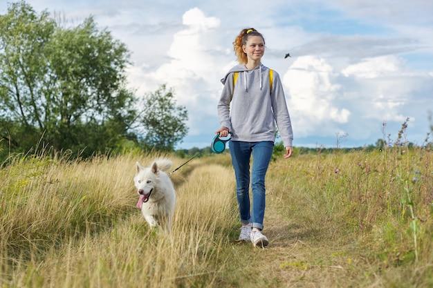 Aktiver gesunder lebensstil, jugendliches mädchen, das mit weißem huskyhund, raum schöne landschaft mit blauem bewölktem himmel und gelbem verbranntem gras geht