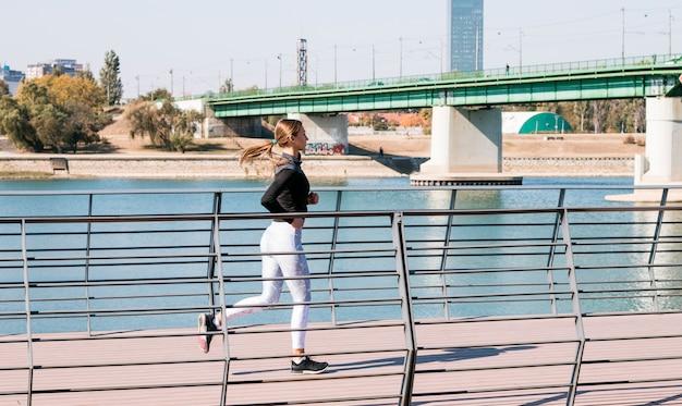 Aktiver gesunder weiblicher läufer, der an im freien rüttelt
