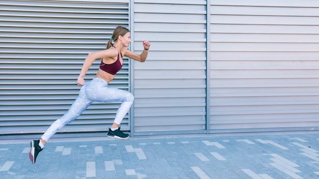 Aktiver gesunder weiblicher läufer, der vor fensterladen rüttelt