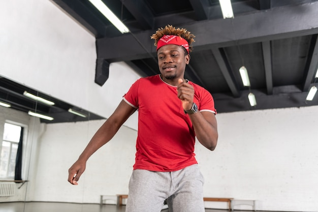 Aktiver, gut aussehender junger tänzer, der seine leistung routinemäßig wiederholt, während er rote accessoires hat