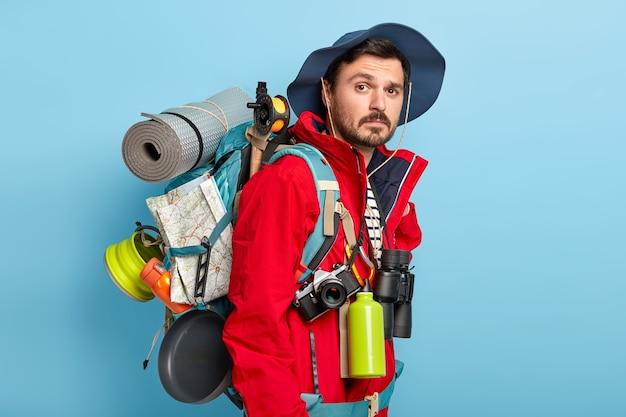 Aktiver gutaussehender mann mit schnurrbart und borsten, trägt einen touristenrucksack auf dem rücken, geht im wald spazieren, hat eine wanderung, trägt eine rote jacke und einen hut