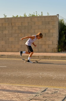 Aktiver junge, der skateboard entlang der fahrbahn reitet