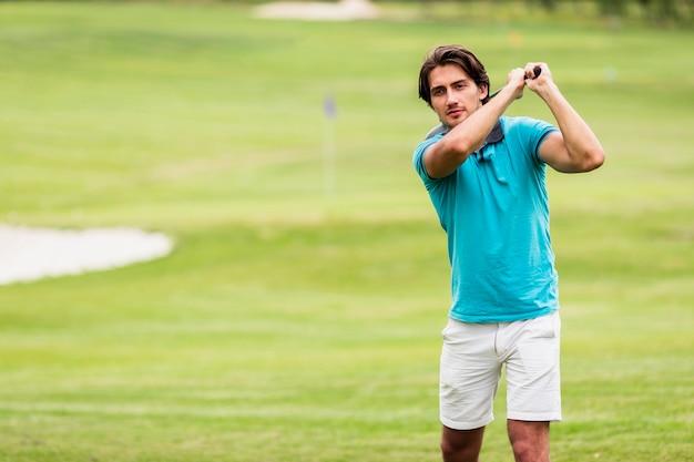 Aktiver junger mann, der golf spielt