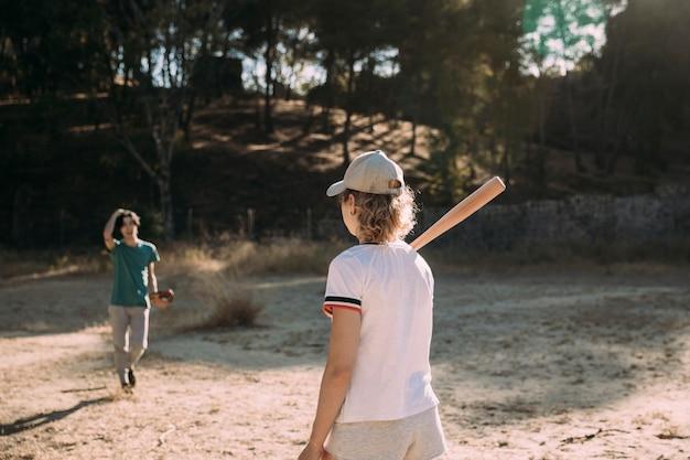 Aktiver junger mann und frau, die draußen baseball spielt