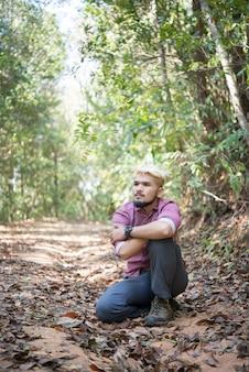 Aktiver junger mann wanderer nehmen einige ruhe mit der natur nach dem gehen, obwohl der wald.