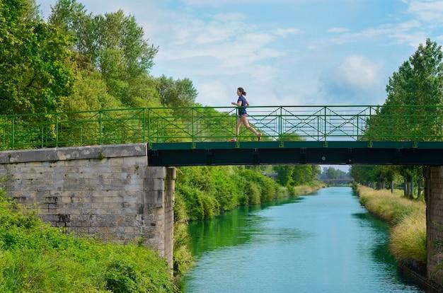 Aktiver läufer der frau, der über flussbrücke, laufen im freien, sport, fitness und gesundes lebensstilkonzept joggt