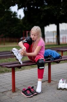Aktiver lebensstil in einer modernen stadt, mädchen zieht rollschuhe im stadion an