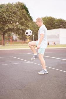 Aktiver lebensstil in einer modernen stadt - sportmann, der mit einem fußball am stadion spielt