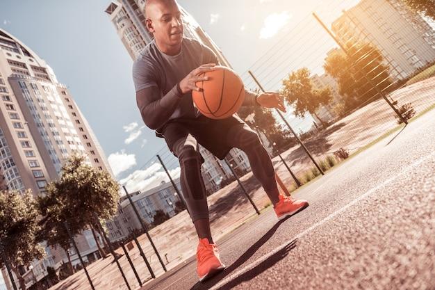 Aktiver lebensstil. netter junger mann, der basketballspiel spielt, während er seine fähigkeiten entwickelt