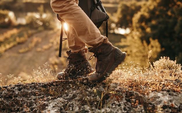 Aktiver männlicher rucksacktourist in trekkingstiefeln, die auf spur gehen