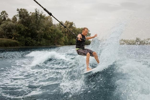 Aktiver mann, der auf dem wakeboard reitet und ein seil hält