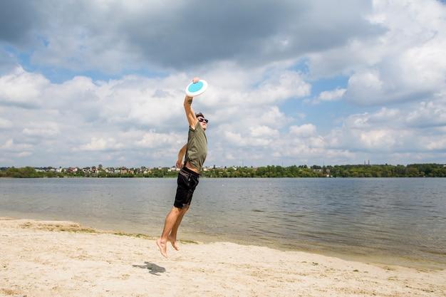 Aktiver mann, der frisbee auf sandigem strand spielt