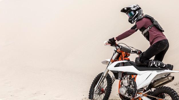Aktiver mann, der motorrad in der wüste reitet