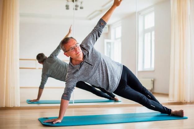 Aktiver mann, der übungen tut, um fit zu bleiben