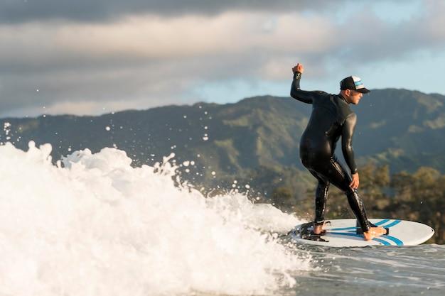 Aktiver mann in spezialausrüstung beim surfen in hawaii ha