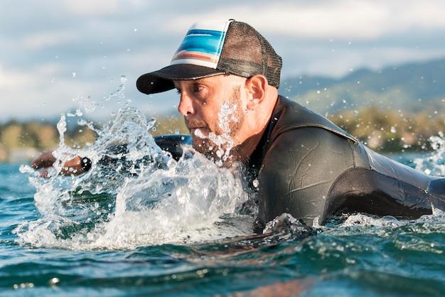 Aktiver mann in spezialausrüstung, der auf einem surfbrett bleibt staying