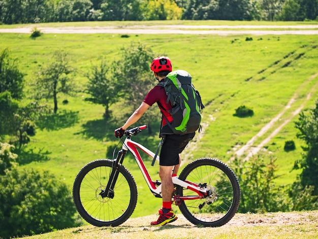 Aktiver mann mit rucksack, der vollgefedertes fahrrad auf natürlichem hintergrund fährt